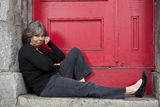 woman-sitting-door-stoop-21005133